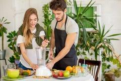 Молодые пары используя juicer стоковое фото