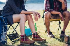 Молодые пары и друг сидя на стуле обсуждают совместно campin Стоковая Фотография