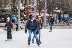 Молодые пары катаясь на коньках на общественном катании на коньках rink outdoors Стоковые Фото