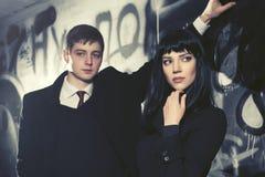Молодые пары моды стоя рядом с стеной граффити Стоковое Изображение