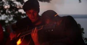 Молодые пары наслаждаясь воссозданием - укомплектуйте личным составом играть гитару и около костра на ноче акции видеоматериалы