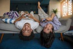Молодые пары наслаждаясь играющ видеоигры совместно стоковые фотографии rf