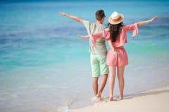 Молодые пары на белом пляже во время летних каникулов Счастливая семья наслаждается их медовым месяцем Стоковое Фото