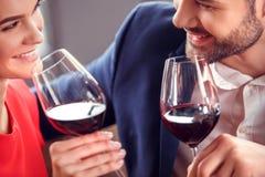 Молодые пары на дате в вине ресторана сидя выпивая flirting жизнерадостный конец-вверх стоковая фотография