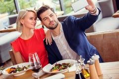 Молодые пары на дате в обедать ресторана сидя держащ смартфон принимая представлять фото selfie радостный стоковое фото