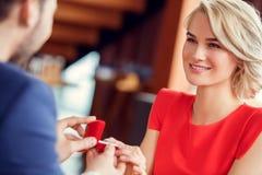 Молодые пары на дате в ресторане сидя держащ коробку кольца смотря конец-вверх одина другого счастливый стоковое фото rf