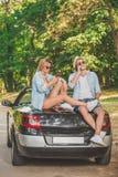 Молодые пары на поездке используя smartphones кресло принципиальной схемы наслаждаясь женщиной уклада жизни самомоднейшей довольн стоковое фото