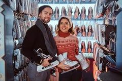Молодые пары нося теплые одежды стоя около шкафа с много пар коньков, выбирая его размер стоковое фото rf
