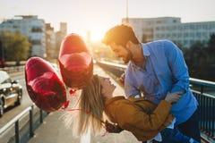 Молодые пары обнимая датировка и целовать внешний стоковое изображение