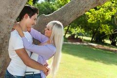 Молодые пары обнимая под деревом. Стоковое Фото