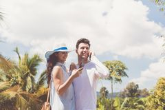 Молодые пары обнимая Outdoors используя телефонный звонок человека Smartphones клетки говоря пока беседовать женщины онлайн Стоковые Фотографии RF