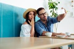 Молодые пары околпачивая вокруг, принимающ selfies - Изображение стоковая фотография rf
