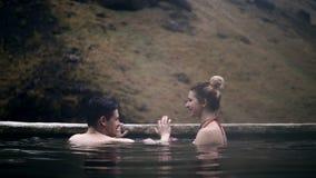Молодые пары ослабляя в горячих источниках в Исландии Путешествовать плавание человека и женщины в долине гор, романтичная дата видеоматериал
