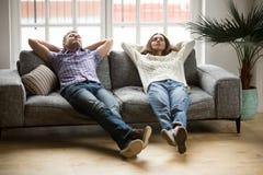 Молодые пары ослабляя совместно на софе наслаждаясь ворсиной дышая Стоковые Фотографии RF