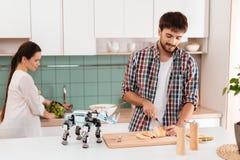 Молодые пары подготавливая еду в современной светлой кухне Робот на переднем плане Стоковые Изображения RF