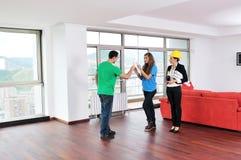 Молодые пары покупая новый дом с агентом по продаже недвижимости Стоковое Изображение