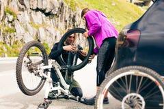 Молодые пары получая их велосипеды готовый стоковые фотографии rf