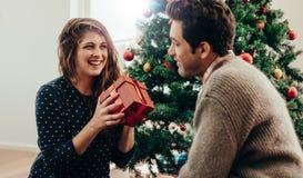 Молодые пары празднуя рождество дома Стоковая Фотография