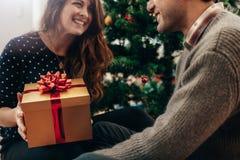 Молодые пары празднуя рождество путем обменивать подарки Стоковая Фотография