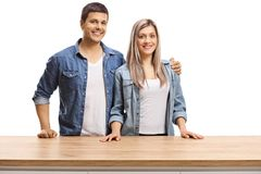 Молодые пары представляя за деревянной стойкой стоковая фотография