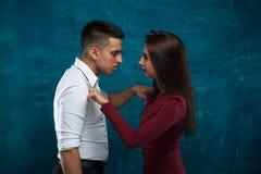 Молодые пары представляя на голубой предпосылке Стоковая Фотография
