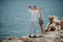 Молодые пары принимая фото автопортрета selfie на верхней части скалы на предпосылке океана Счастливые любовники, женщина и челов стоковое изображение