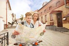 Молодые пары при самокат смотря карту Стоковая Фотография RF