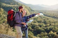 Молодые пары путешествуя совместно в горах Счастливый человек хипстера и его девушка с рюкзаками планируя маршрут мимо стоковая фотография