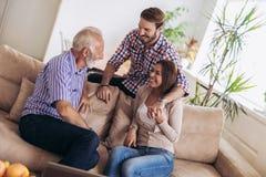 Молодые пары разговаривая с их старшим отцом стоковые изображения rf