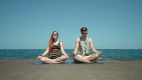 Молодые пары размышляя сидеть на пристани пляжем Праздники с занятиями йогой акции видеоматериалы