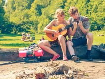 Молодые пары располагаясь лагерем играющ гитару внешнюю Стоковое фото RF
