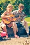 Молодые пары располагаясь лагерем играющ гитару на открытом воздухе стоковые изображения rf