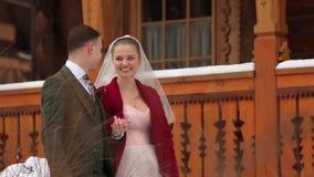 Молодые пары свадьбы идя, усмехаясь и говоря держащ руки на лестницах на деревне лыжного курорта с деревянными коттеджами сток-видео