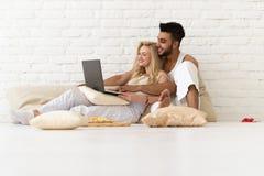 Молодые пары сидят на поле подушек, испанском человеке и женщине используя спальню любовников портативного компьютера Стоковые Фото