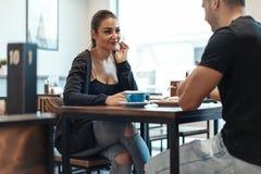 Молодые пары сидя в кафе на дате, выпивая кофе и есть десерт стоковые фото