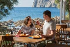 Молодые пары сидя в кафе около моря Стоковая Фотография RF