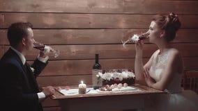 Молодые пары сидя в ресторане на таблице и выпивая вине сток-видео