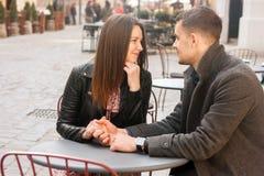 Молодые пары сидя на кафе улицы Романтичная дата стоковые изображения