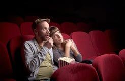 Молодые пары сидя на красном кинотеатре стоковое фото rf