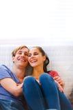 Молодые пары сидя на кресле и смеяться над Стоковое Изображение RF