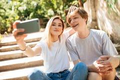 Молодые пары сидя на лестницах в парке и делая смешное selfie совместно Усмехаясь мальчик и красивая девушка с светлыми волосами Стоковые Изображения