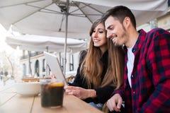 Молодые пары сидя на террасе Стоковые Изображения