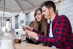 Молодые пары сидя на террасе Стоковые Фото