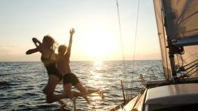 Молодые пары скача от плавать яхта в открытое море на заходе солнца стоковое изображение