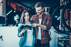 Молодые пары смотрят каталог выбирают новый велосипед стоковое изображение rf
