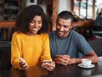 Молодые пары смотря мобильный телефон стоковое изображение rf