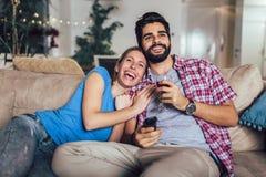 молодые пары смотря ТВ в живущей комнате стоковое фото