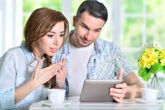 Молодые пары смотря цифровую таблетку Стоковое Фото