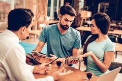 Молодые пары советуя с с продавцом мебели стоковое изображение