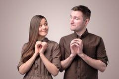 Молодые пары со злокозненными и grinning сторонами усмехаются стоковые фотографии rf